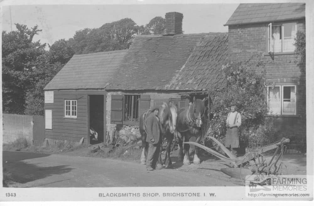 Sepia postcard showing men, horses and plough outside blacksmith's shop Brighstone, IW