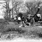 Glass negative of men working with two horses harnessed to heavy log cart