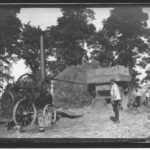 Photographic print taken from a glass plate negative in the collection of men working a threshing machine driven by a steam engine