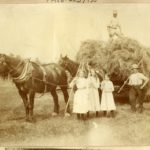 Sepia photograph showing a haymaking scene, with loaded wagon, two horses, three men, three girls and their implements