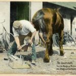 Tinted photograph shows a blacksmith shoeing a horse, with tools and a bicycle visible in the background