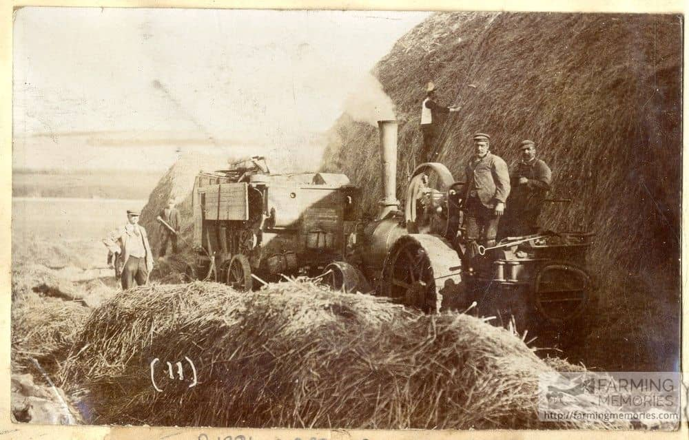 A sepia photograph showing good detail of a threshing machine, crew and steam engine
