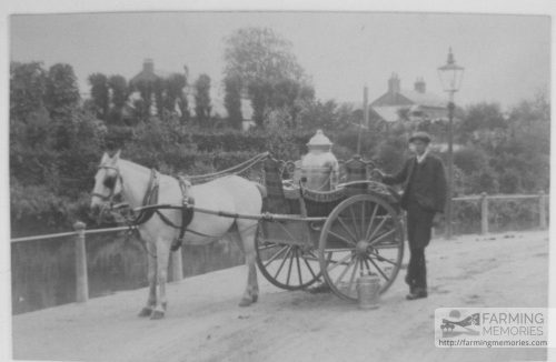 Sepia photograph showing George Guy (aged 16) standing beside Mr Morris's milk float, Newport