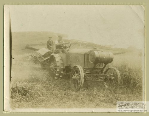 Black and white photograph of two men sat on an early tractor with farming equipment behind in a field